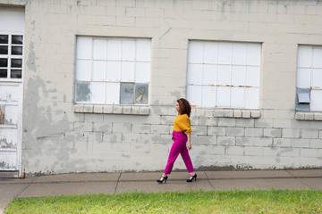 Woman in vibrant clothing walking on urban sidewalk