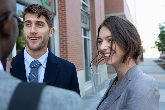 Professional couple talking to business colleague on pavement