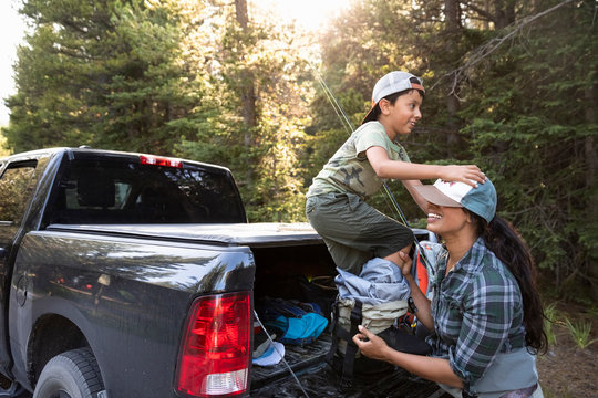 Playful mother helping son put on waders at back of pickup truck