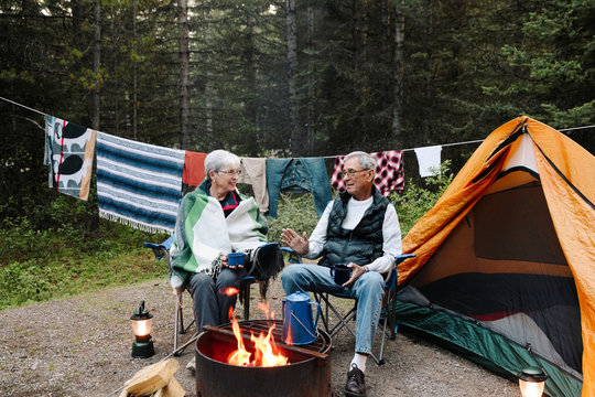 Senior couple relaxing and talking at campsite campfire