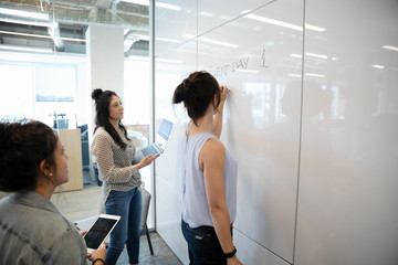 Businesswomen brainstorming at whiteboard in conference room meeting