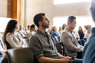 Businessman with smart phone listening in conference audience