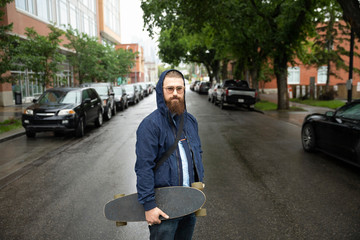 Portrait confident hipster man with skateboard on wet urban street
