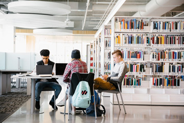 Three students studying in university library