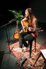 Female musician playing guitar and singing on stage