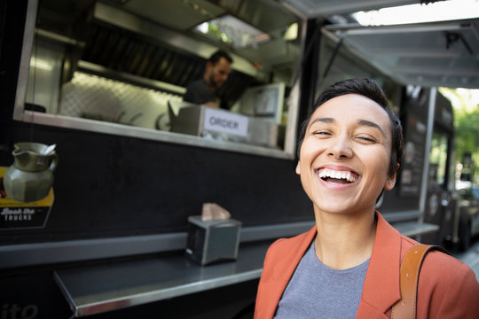 Portrait smiling, confident young woman outside Food truck