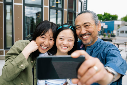 Happy parents and down syndrome daughter taking selfie with camera phone on sidewalk