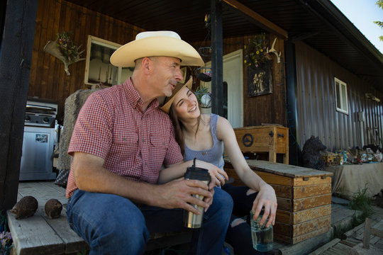 Father and daughter wearing cowboy hats sitting outside ranch house