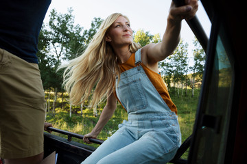 Young woman sitting in back of pickup truck