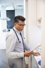 Focused male doctor reviewing medical record in clinic