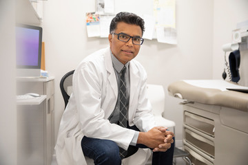 Portrait confident male doctor in clinic examination room