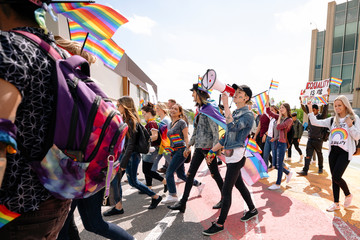 Group of students with rainbow flags and megaphone on gay pride march