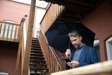 Man with smart phone and umbrella on apartment stairs
