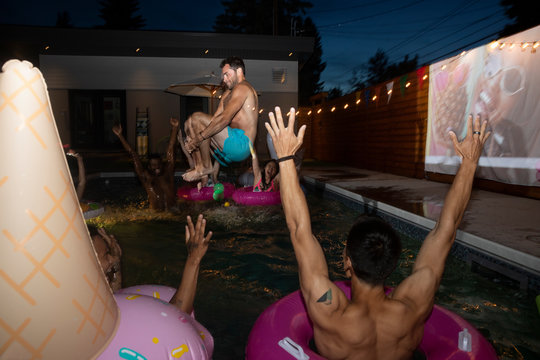 Friends cheering for carefree young man jumping into summer swimming pool at night