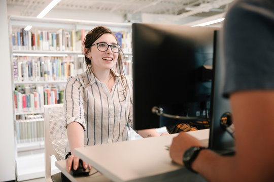 Library staff using computer and smiling at student