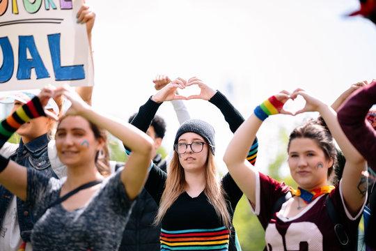 Students making heart shapes with hands at gay pride parade