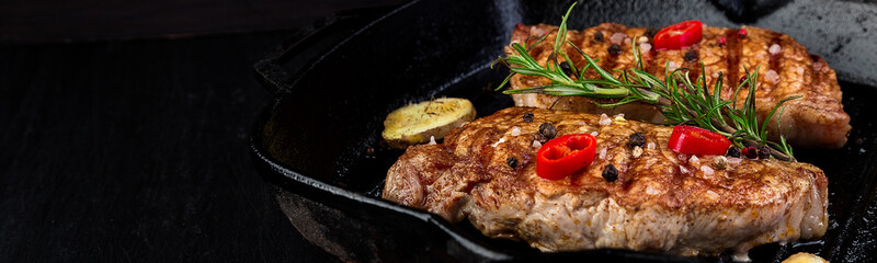 Banner with Grilled pork steak in grill pan with rosemary, pepper chilli and ginger on wooden board.