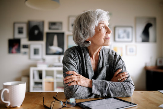 Thoughtful senior woman with digital tablet looking away