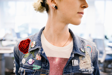 Student wearing denim jacket with badges close up