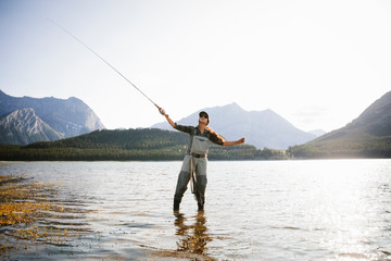 Woman fly fishing in sunny, scenic lake Wall mural