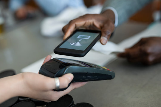 Businessman paying contactless with smart phone