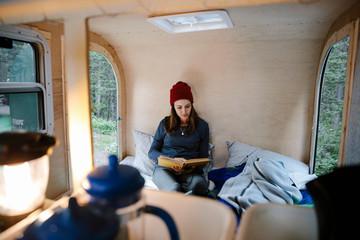 Woman relaxing, reading book on bed in camper van