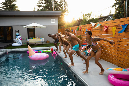 Playful young adult friends jumping into summer, sunny swimming pool