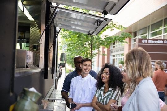 Smiling customers waiting outside Food truck