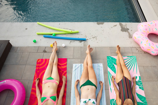Young women friends relaxing, sunbathing at summer poolside