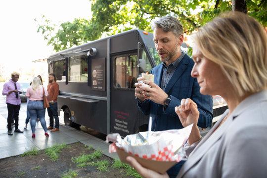 Business people eating burritos outside Food truck