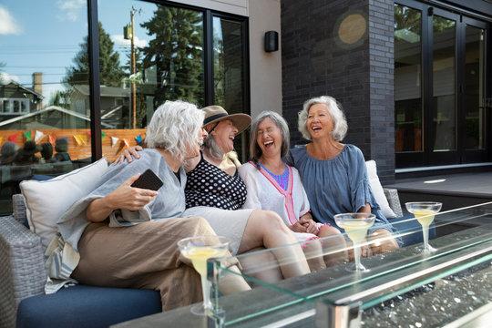 Laughing, carefree senior women friends drinking margaritas on summer patio