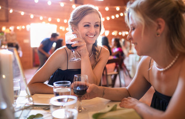 Happy young woman drinking red wine at wedding reception