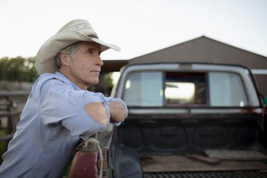 Mature man wearing cowboy hat leaning on pickup truck