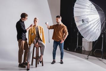 photographer shooting how Makeup Artist doing makeup to stylish model Wall mural