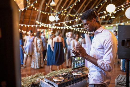 Male DJ using smart phone, working wedding reception
