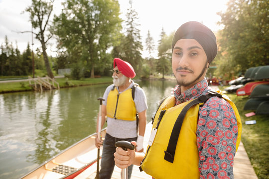 Portrait of young Indian man wearing life jacket and turban looking at camera
