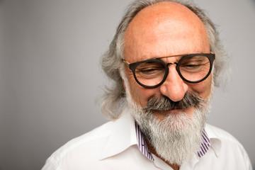 Portrait smiling, happy senior man with eyeglasses and gray beard