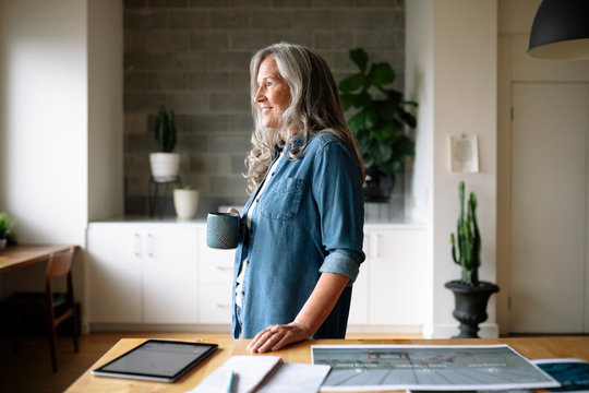 Smiling, confident creative female designer drinking coffee in office
