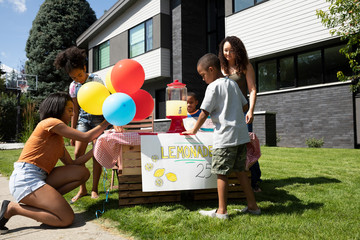 Family setting up lemonade stand in sunny, summer front yard of house