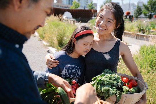 Happy, affectionate young woman with Down syndrome harvesting fresh vegetables with family in sunny garden