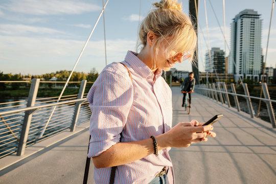Young woman using smart phone on sunny, urban bridge