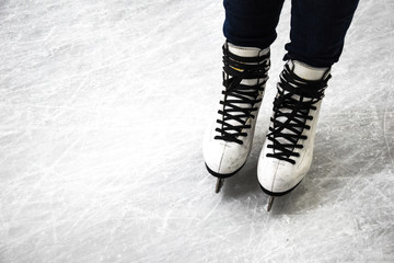 Female legs in white ice skates, Ice skater on the skating rink, Winter sport, close up of legs in skates on skating rink, Copy space