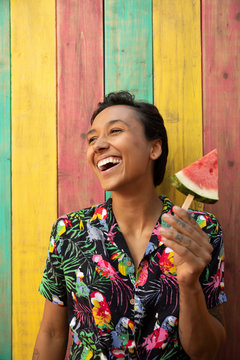Portrait carefree young woman eating watermelon slice on summer patio