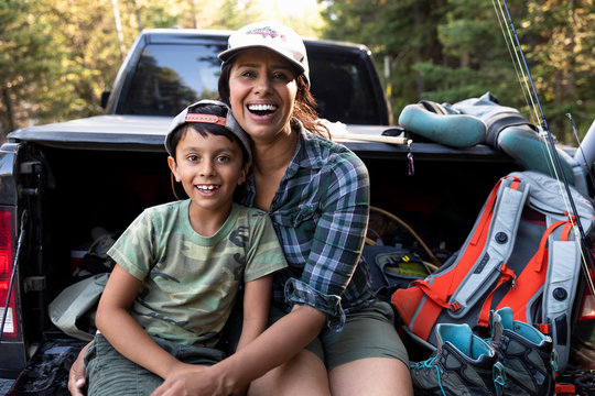 Portrait happy mother and son with fishing equipment at back of pickup truck