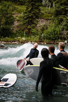 Male surfer teaching group river surfing