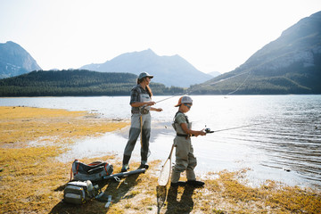 Mother and son fishing at sunny, scenic lakeside