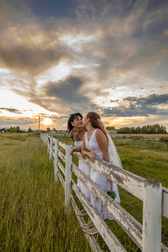 Happy, affectionate lesbian brides standing at rural fence