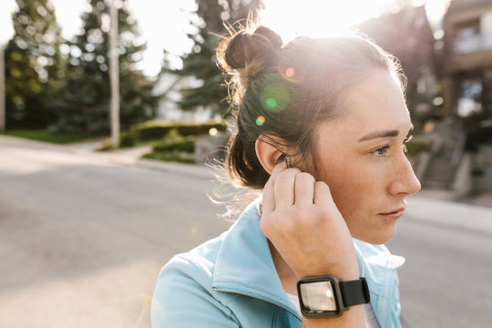 Mid adult woman wearing smart watch placing earphone in ear