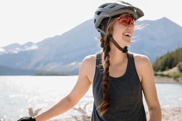 Happy woman in mountain biking helmet at sunny lakeside