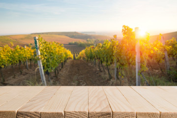 Keuken foto achterwand Wijngaard sunny landscape of vineyard with green leaves and bottles of wine on table
